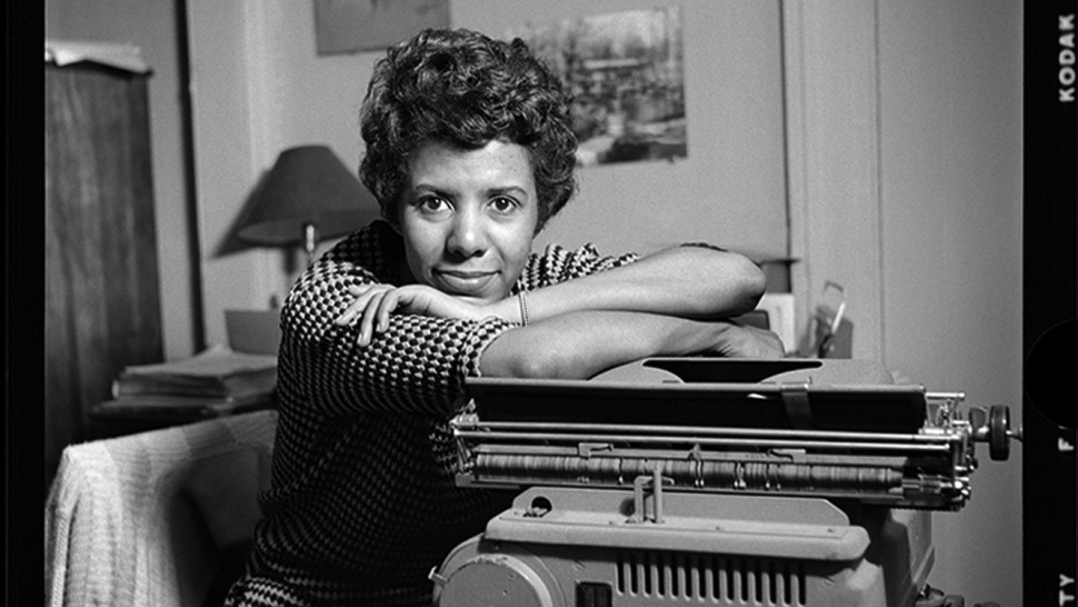 black and white photo of Hansberry leaning on an old typewriter