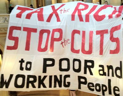 White banner with Tax the Rich, Stop the Cuts to poor and working people